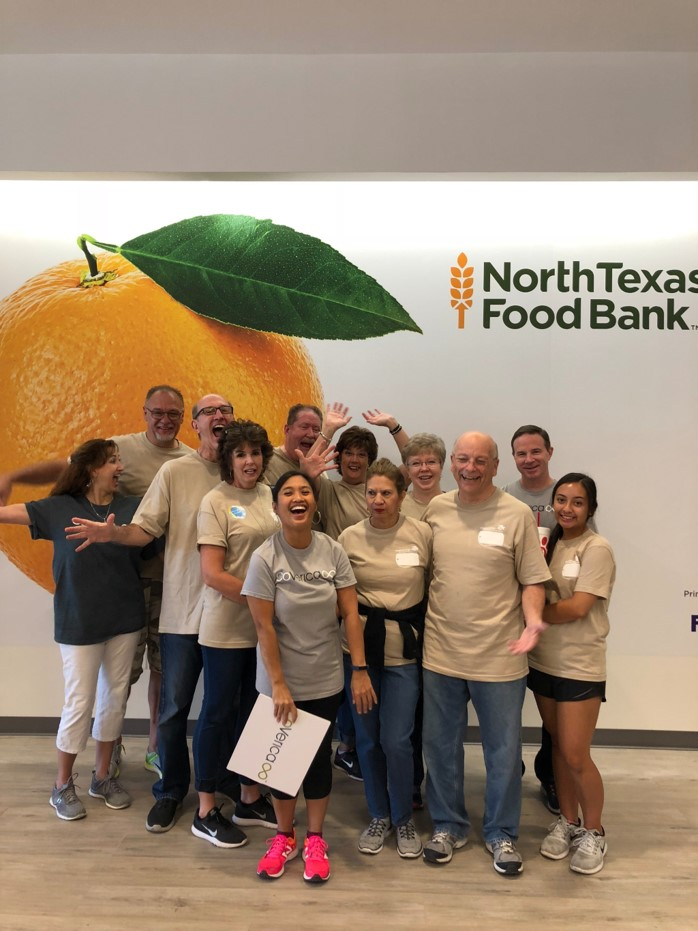 "A group of twelve people standing together and smiling in front of a wall that says ""North Texas Food Bank"""