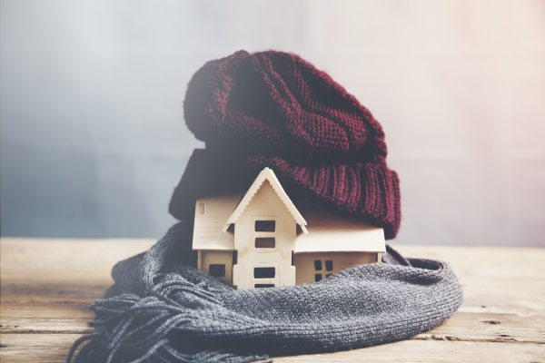 small wooden house wrapped in a scarf with a wool red hat on top
